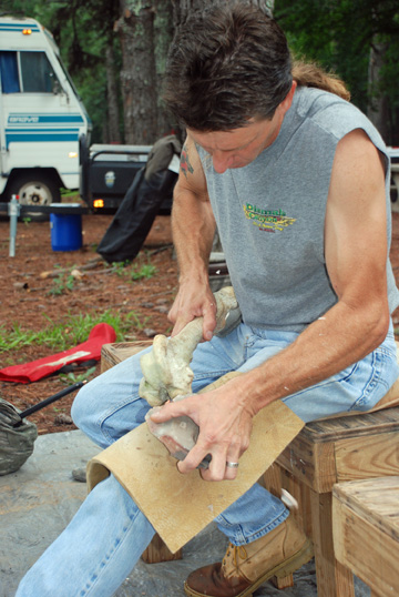 A modern flintknapper shapes a stone tool.