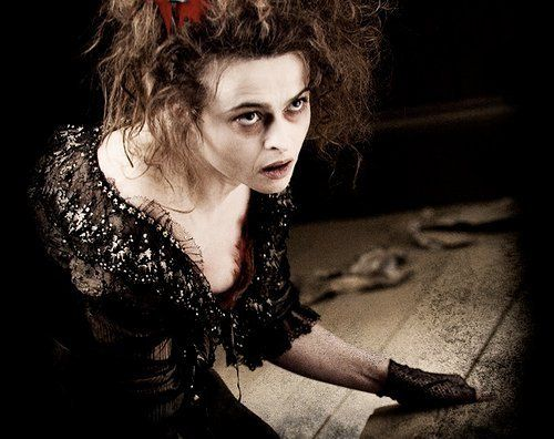 Mrs. Lovett in Sweeney Todd as portrayed by Helena Bonham Carter, leaning over a table and looking up